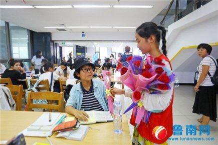 志愿者送玫瑰,图书馆盛开文明之花